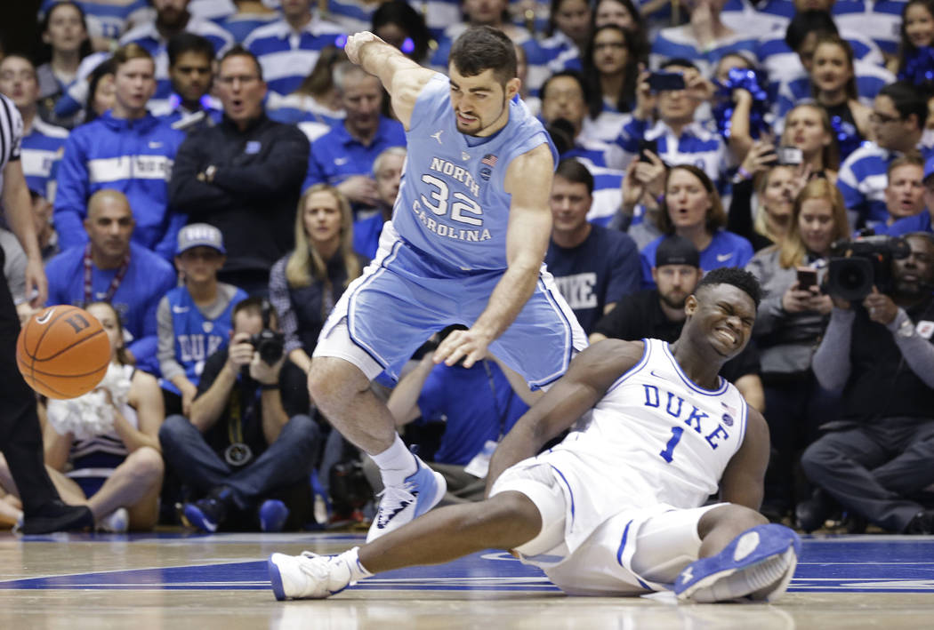 Duke's Zion Williamson (1) falls to the floor with an injury while chasing the ball with North Carolina's Luke Maye (32) during the first half of an NCAA college basketball game in Durham, N.C., W ...