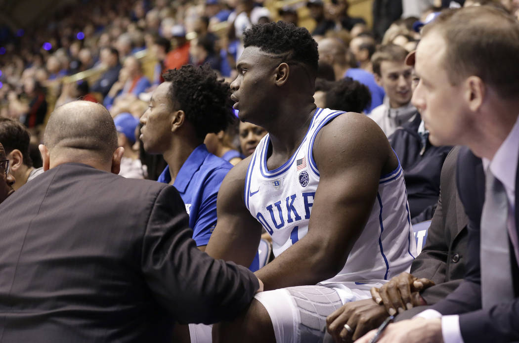 Duke's Zion Williamson (1) is attended to on the bench following an injury during the first half of an NCAA college basketball game against North Carolina in Durham, N.C., Wednesday, Feb. 20, 2019 ...