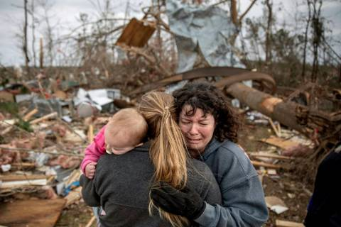 Carol Dean, right, cries while embraced by Megan Anderson and her 18-month-old daughter Madilyn, as Dean sifts through the debris of the home she shared with her husband, David Wayne Dean, who die ...