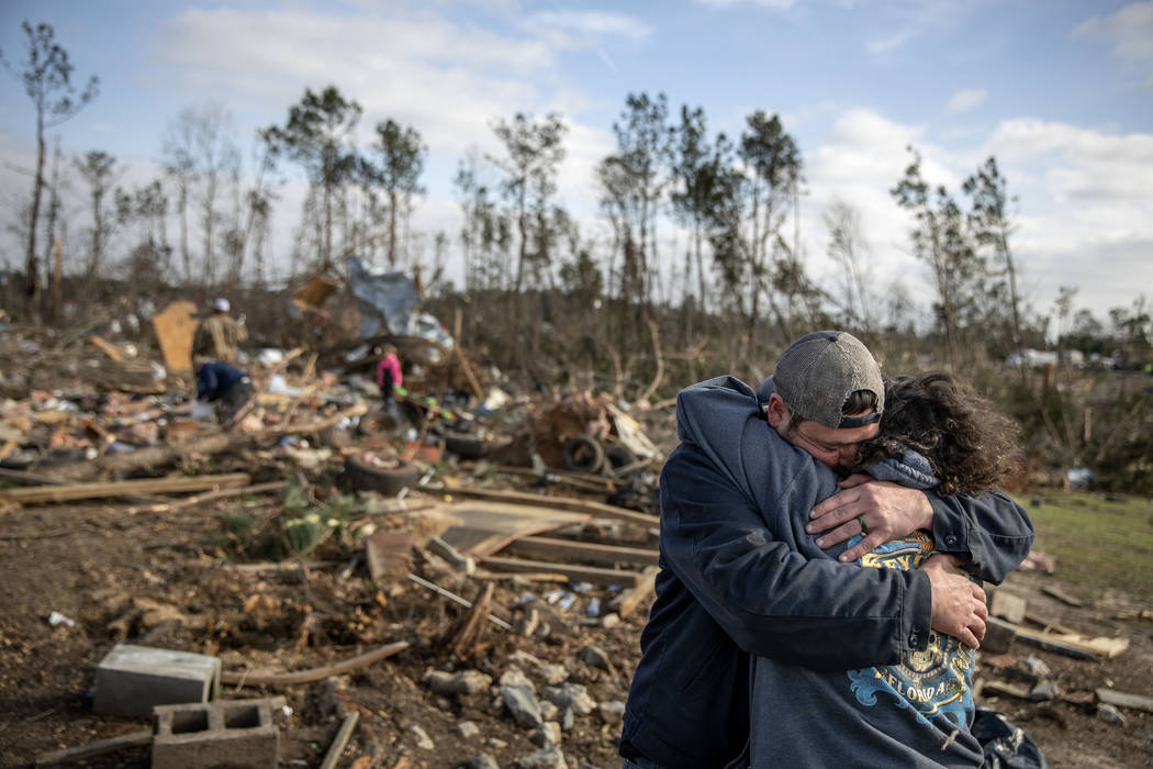 ADDED SHARED WITH-Carol Dean, right, is embraced by David Theo Dean as they sift through the debris of the home Carol shared with her husband and David's father, David Wayne Dean, who died when a ...