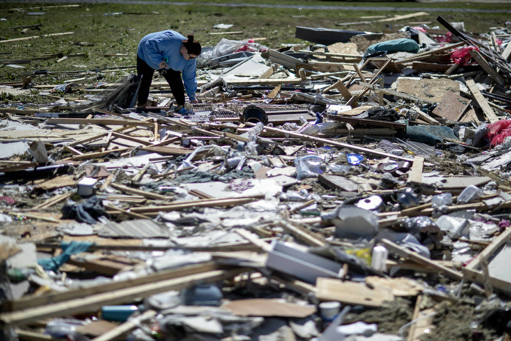Kayla Causey sifts through the debris while helping her mother retrieve personal items after a tornado destroyed her home in Beauregard, Ala., Tuesday, March 5, 2019. (AP Photo/David Goldman)