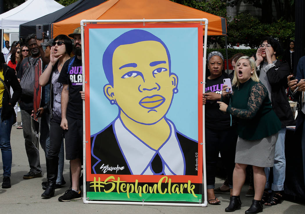 FILE - In this April 9, 2018 file photo protesters display an image of Stephon Clark at a crime victims rights rally, at the Capitol in Sacramento, Calif. Two Sacramento police officers won't face ...
