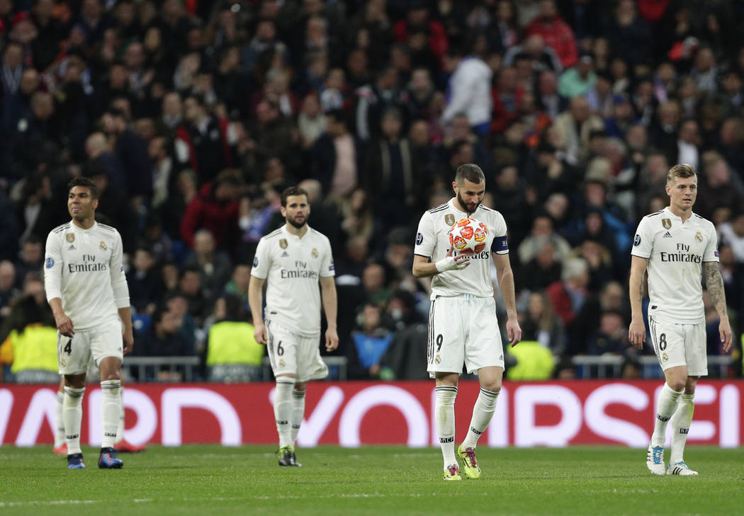 Real forward Karim Benzema holds the ball after being scored by Ajax, during the Champions League soccer match between Real Madrid and Ajax at the Santiago Bernabeu stadium in Madrid, Spain, Tuesd ...