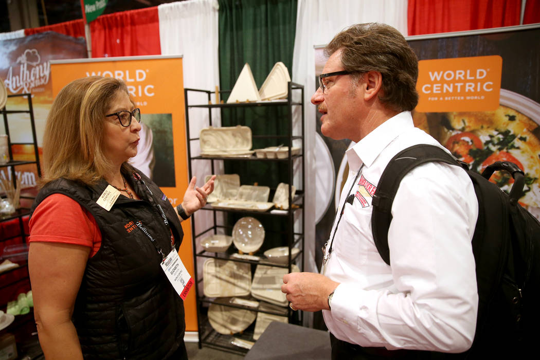 Liz Anderson, vice president of business development for World Centric, talks to Robert Morando of New Cambria, Kansas, in her booth at the International Pizza Expo at the Las Vegas Convention Cen ...