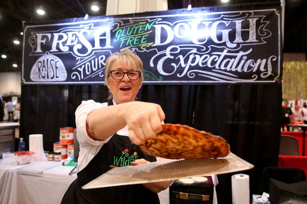 Kim Desch, of Wild Flour Bakery in Longmont, Colorado, shows the bottom of her gluten-free pizza at the International Pizza Expo at the Las Vegas Convention Center Tuesday, March 5, 2019. Desch sa ...