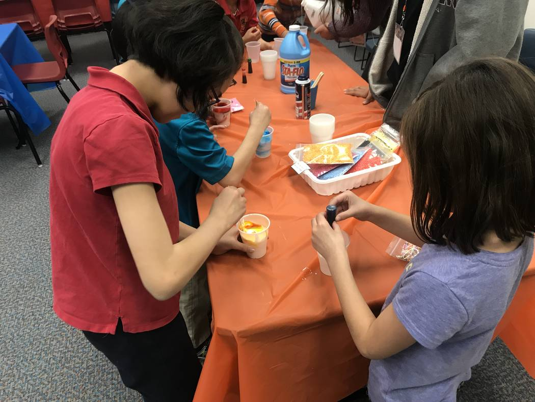 Two children at the Gross World Records event pour food coloring into their glue mixture in an effort to make slime. (Mia Sims-Las Vegas Review-Journal/@miasims___)