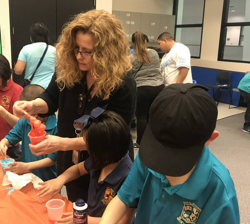 """Kathryn Tilton, a youth services assistant at the Sahara West Library, helps children make slime after a presentation on on the world's most """"gross"""" records. (Mia Sims-Las Vegas Review-Journal/@mi ..."""