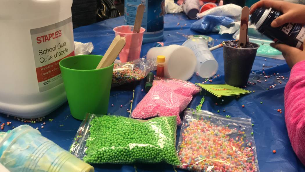 Library volunteers helped children and parents make slime. Glue, foam beads, slime and sticks covered the tables as the children toyed with the decorated goo in their hands. (Mia Sims-Las Vegas Re ...