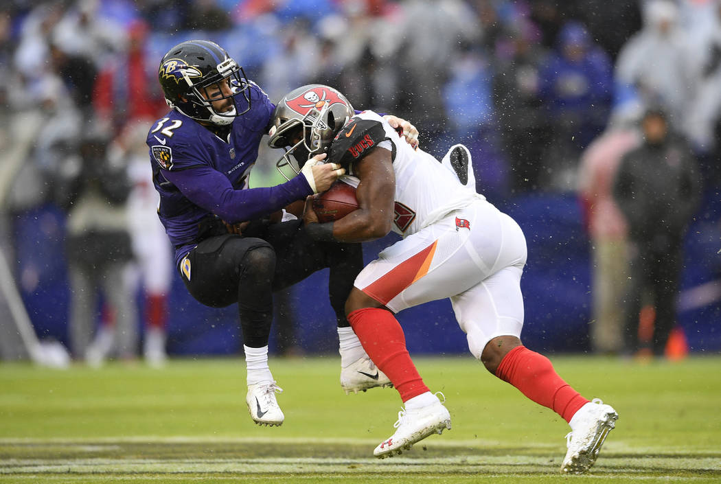 Tampa Bay Buccaneers running back Peyton Barber, right, rushes against Baltimore Ravens free safety Eric Weddle in the first half of an NFL football game, Sunday, Dec. 16, 2018, in Baltimore. (AP ...