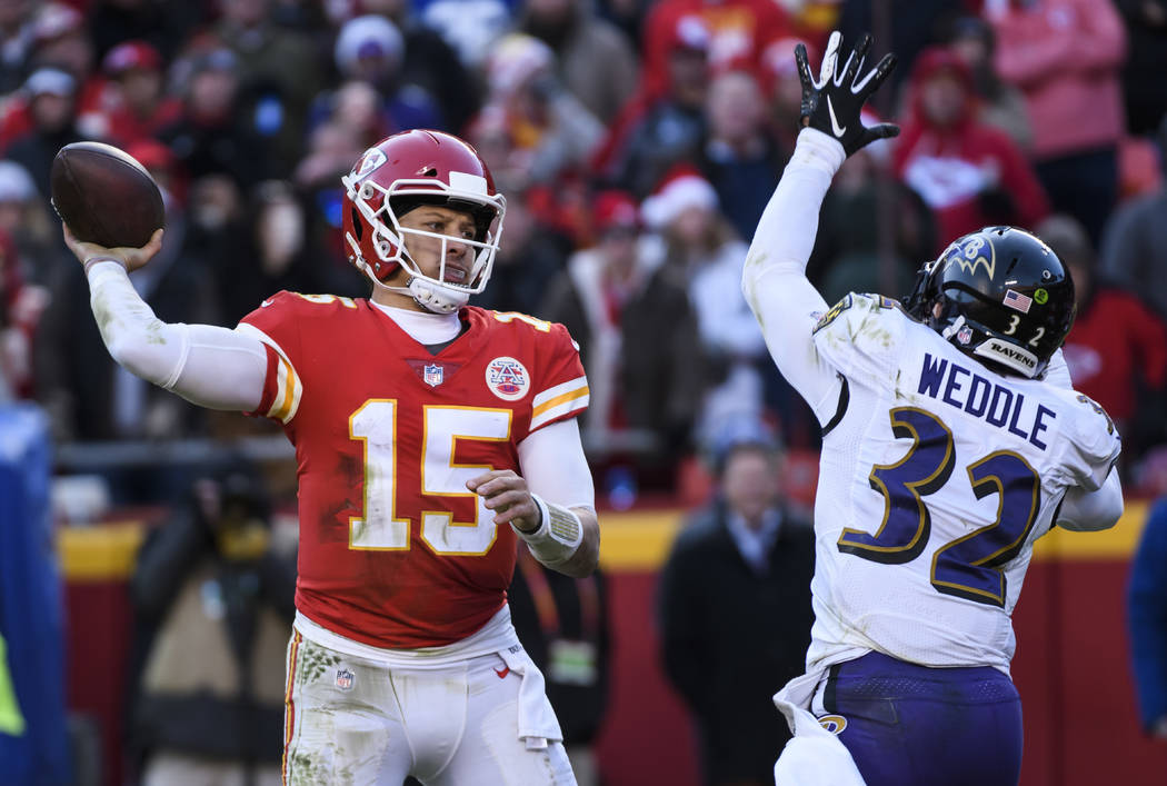 Kansas City Chiefs quarterback Patrick Mahomes (15) is pressured by Baltimore Ravens free safety Eric Weddle (32) during an NFL football game in Kansas City, Mo., Sunday, Dec. 9, 2018. (AP Photo/R ...