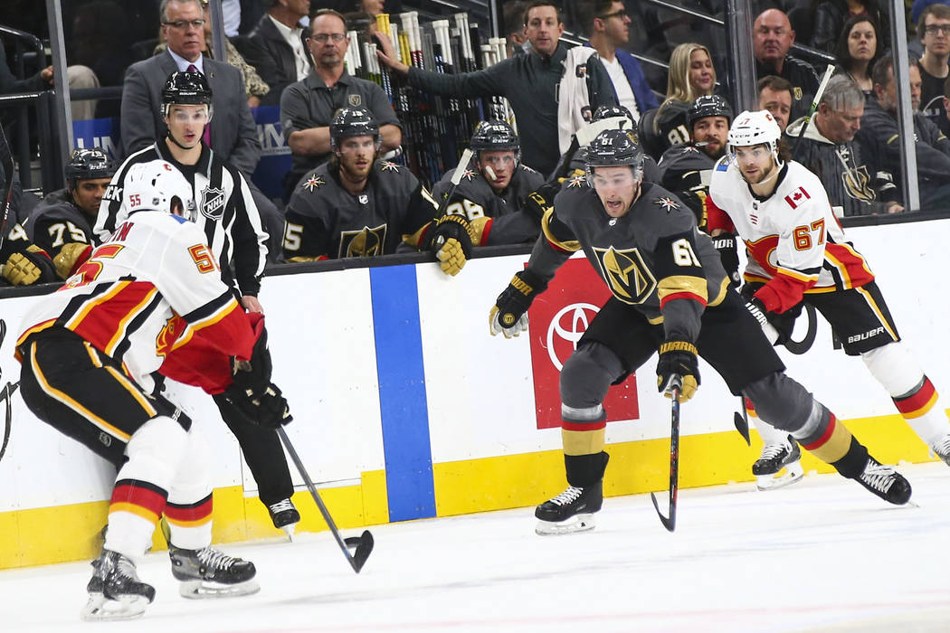 Golden Knights right wing Mark Stone (61) chases after the puck against Calgary Flames defenseman Noah Hanifin (55) and right wing Michael Frolik (67) during the first period of an NHL hockey game ...