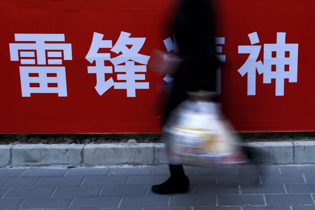 "A woman carries her groceries past a Chinese propaganda board depicting ""Lei Feng Spirit"" on a pavement in Beijing, Tuesday, March 5, 2019. Fast food chain KFC is memorializing a popular ..."