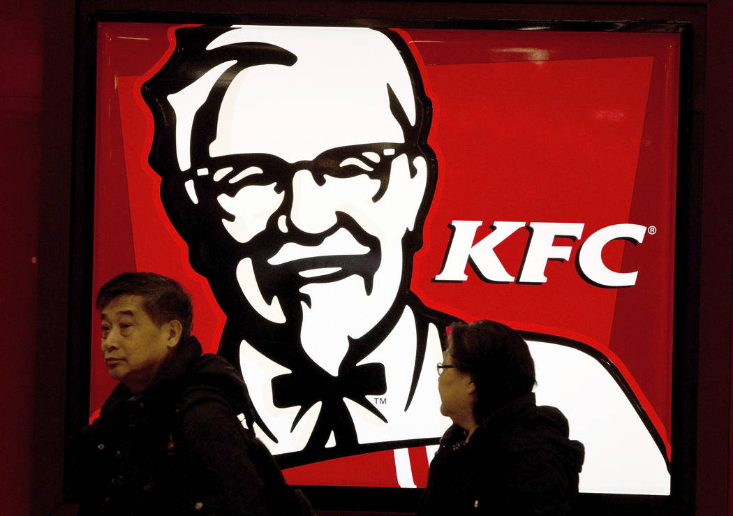 CAPTION CORRECTION CORRECTS OPENING DAY: FILE - In this Monday, Feb. 25, 2013, file photo, a Chinese couple walk past a KFC restaurant at a shopping mall in Beijing. The official Xinhua News Agenc ...