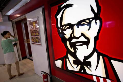 "In this July 31, 2014, file photo, a woman looks at a menu with words ""everyday half-price"" in front of a KFC fast food restaurant in Beijing. The official Xinhua News Agency said the company laun ..."
