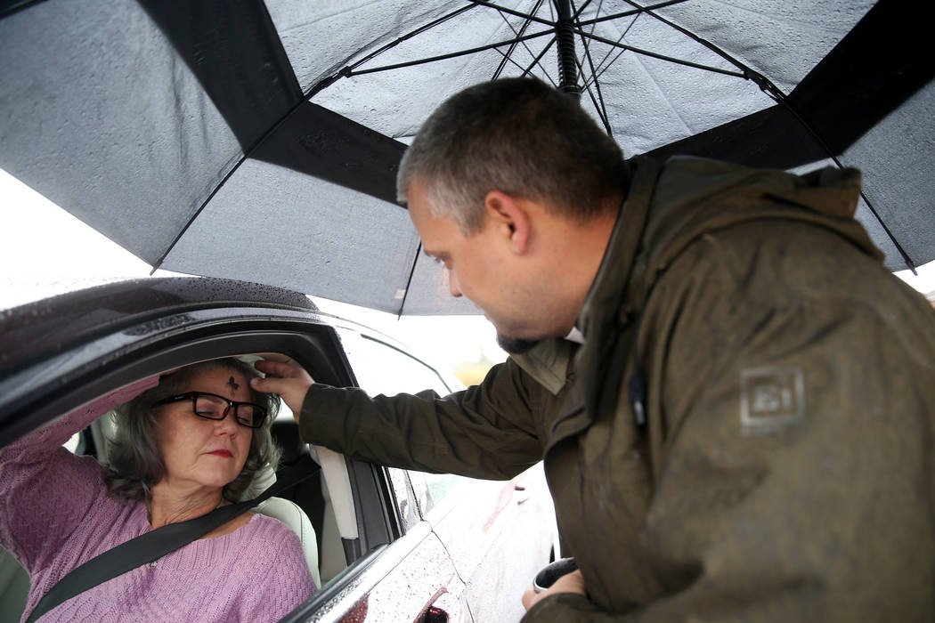 "Pastor Jeremy Nausin applies ashes to Michele Stephenson of Las Vegas at Holy Spirit Lutheran Church during an ""Ashes to Go"" drive-thru Ash Wednesday blessing at the Las Vegas church, Wednesday, M ..."