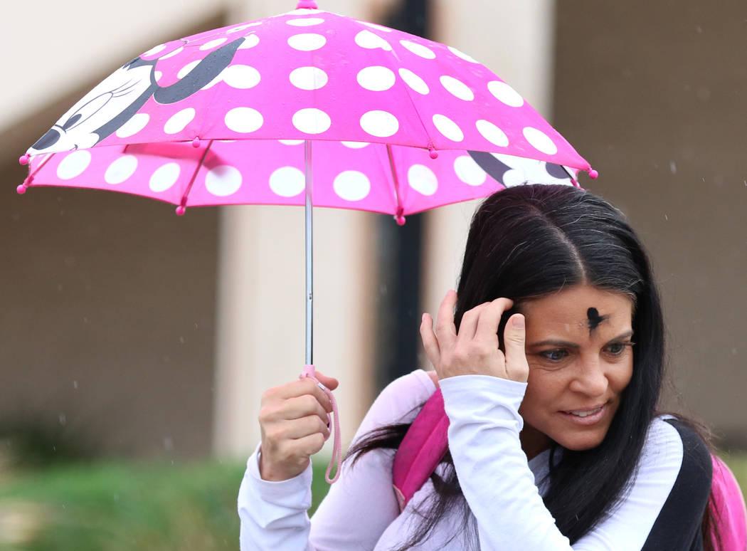 Lori Wood of Las Vegas holds an umbrella to protect herself from rain on Wednesday, March. 6, 2019, in Las Vegas. (Bizuayehu Tesfaye/Las Vegas Review-Journal) @bizutesfaye