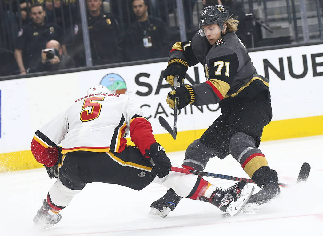 Calgary Flames defenseman Mark Giordano (5) stretches out to block the puck with his skate against Golden Knights center William Karlsson (71) during the first period of an NHL hockey game at T-Mo ...