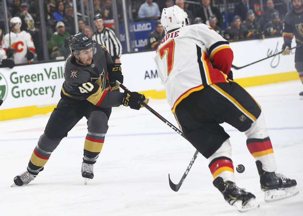 Golden Knights center Ryan Carpenter (40) sends the puck past Calgary Flames defenseman TJ Brodie (7) during the first period of an NHL hockey game at T-Mobile Arena in Las Vegas on Wednesday, Mar ...