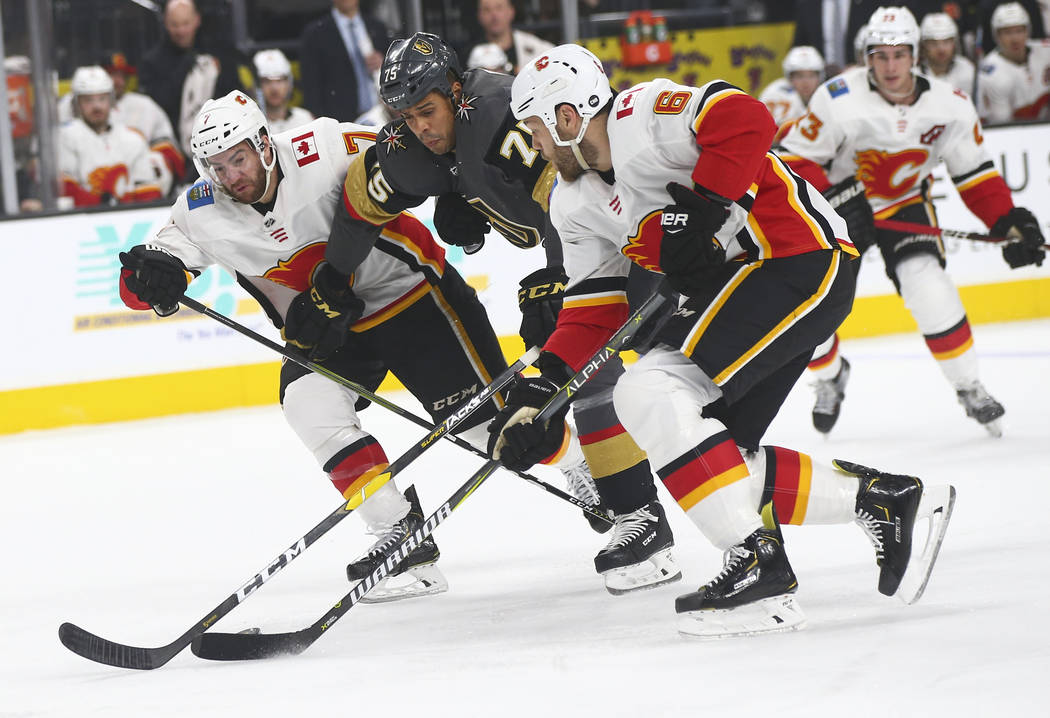 Golden Knights right wing Ryan Reaves (75) battles to keep control of the puck against Calgary Flames defensemen TJ Brodie (7) and Dalton Prout (6) during the first period of an NHL hockey game at ...