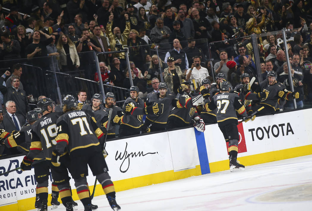Golden Knights defenseman Shea Theodore (27) celebrates his goal with the bench during the first period of an NHL hockey game against the Calgary Flames at T-Mobile Arena in Las Vegas on Wednesday ...