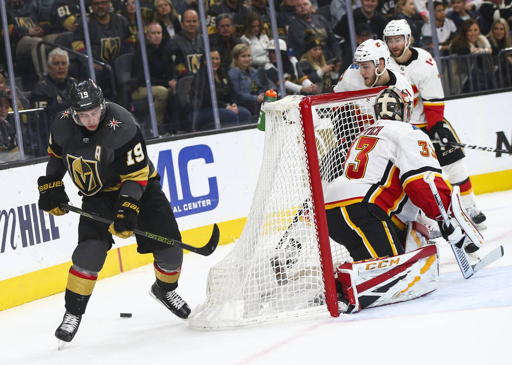 Golden Knights right wing Reilly Smith (19) skates around the net with the puck as Calgary Flames goaltender David Rittich (33) defends during the first period of an NHL hockey game at T-Mobile Ar ...