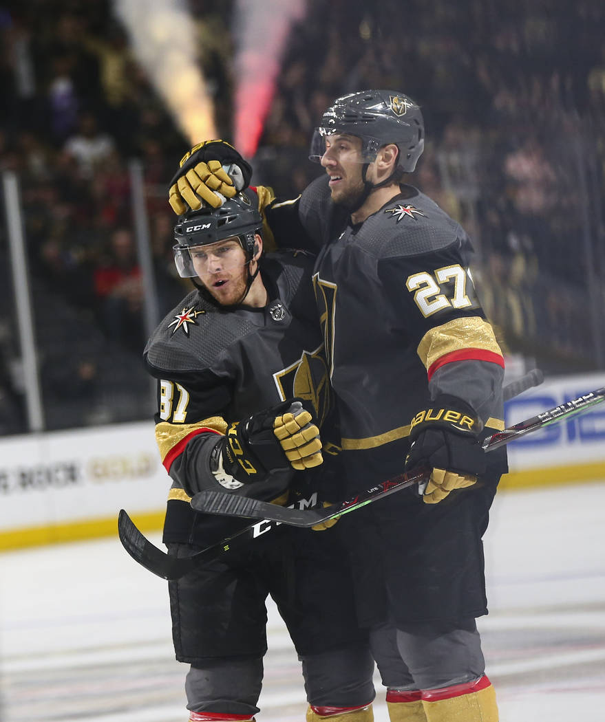 Golden Knights defenseman Shea Theodore (27) celebrates his goal with Golden Knights center Jonathan Marchessault (81) during the first period of an NHL hockey game against the Calgary Flames at T ...