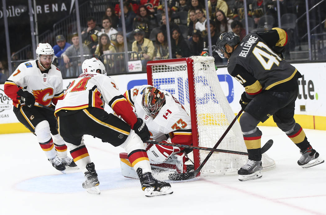 Golden Knights center Pierre-Edouard Bellemare (41) tries to get the puck in against Calgary Flames goaltender David Rittich (33) and Calgary Flames defenseman Travis Hamonic (24) during the secon ...