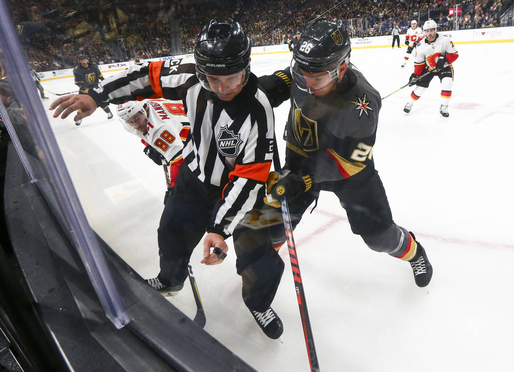 NHL referee Mike Hasenfratz tries to get out of the way of Golden Knights center Paul Stastny (26) and Calgary Flames left wing Andrew Mangiapane (88) as they battle for the puck during the second ...