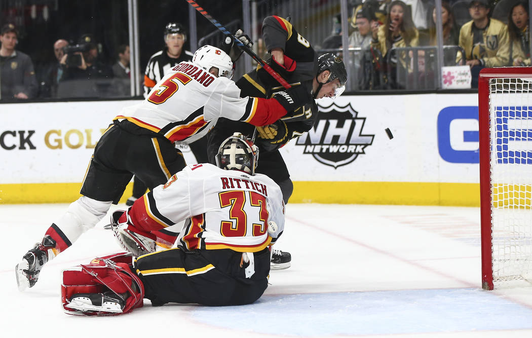 Golden Knights right wing Reilly Smith (19) watches the puck under pressure from Calgary Flames defenseman Mark Giordano (5) as goaltender David Rittich (33) looks on during the second period of a ...