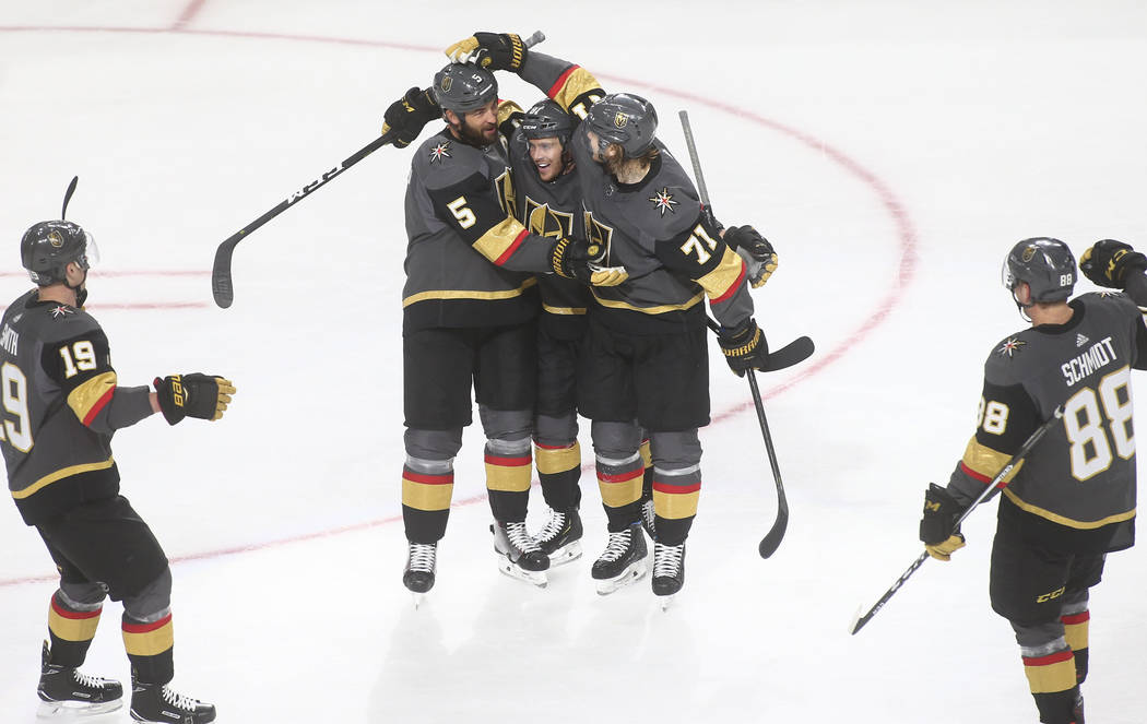 Golden Knights defenseman Deryk Engelland (5) celebrates his goal with Jonathan Marchessault, center, and William Karlsson (71) during the third period of an NHL hockey game against the Calgary Fl ...