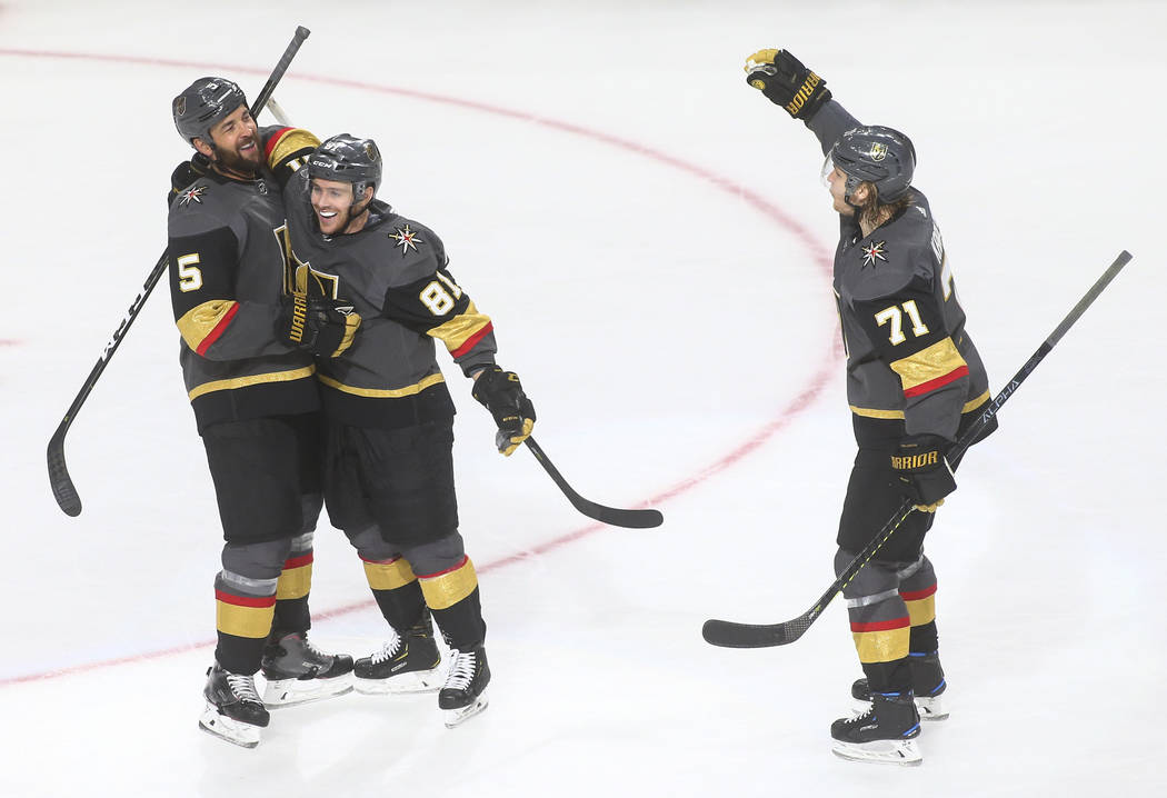Golden Knights defenseman Deryk Engelland (5) celebrates his goal with Jonathan Marchessault (81) and William Karlsson (71) during the third period of an NHL hockey game against the Calgary Flames ...