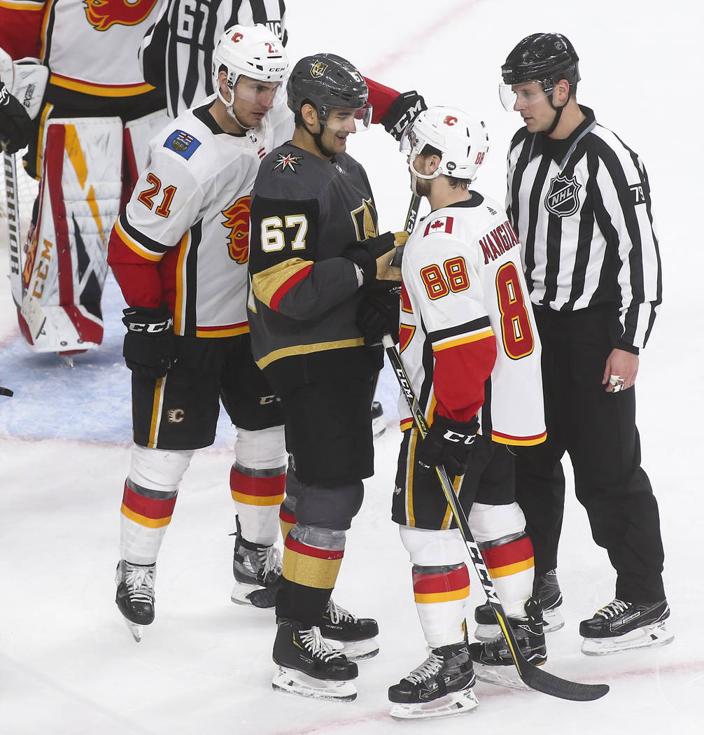 Golden Knights left wing Max Pacioretty (67) reacts while exchanging words with Calgary Flames left wing Andrew Mangiapane (88) while right wing Garnet Hathaway (21) looks on during the third peri ...