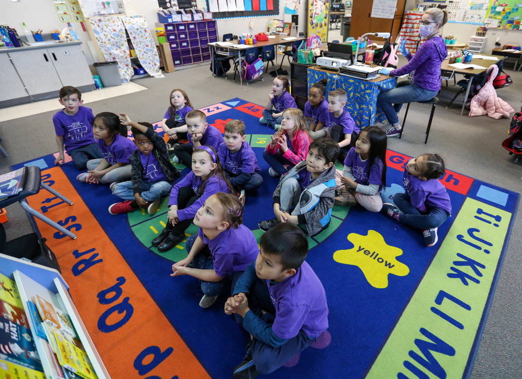 Kindergarten students watch images projecting on the screen as their teacher Nikki McGuire, background, asking them questions during a class at Staton Elementary in Las Vegas, Tuesday, March 5, 20 ...