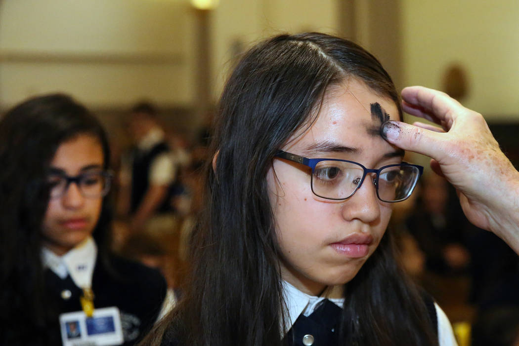 Rev. Larry Lentz applies ashes on St. Viator Parish School student, Jasmine Cortez, forehead at St. Viator Catholic Church during Ash Wednesday on Wednesday, March. 6, 2019, in Las Vegas. Bizuayeh ...