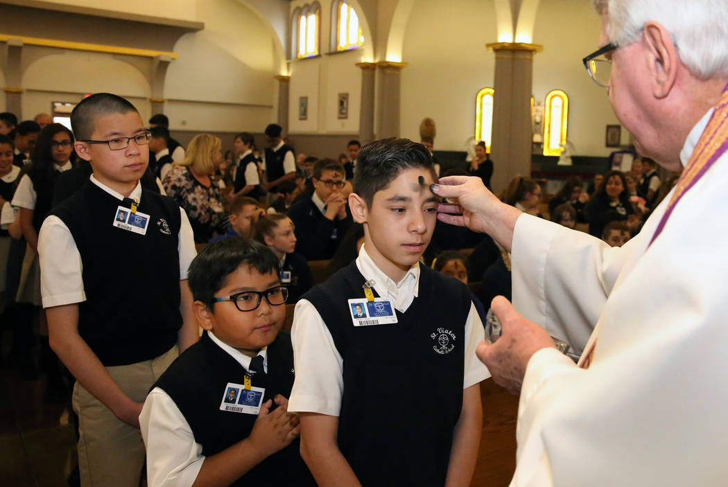 Rev. Larry Lentz applies ashes on St. Viator Parish School student Adrian Galvez forehead at St. Viator Catholic Church during Ash Wednesday on Wednesday, March. 6, 2019, in Las Vegas. Bizuayehu T ...