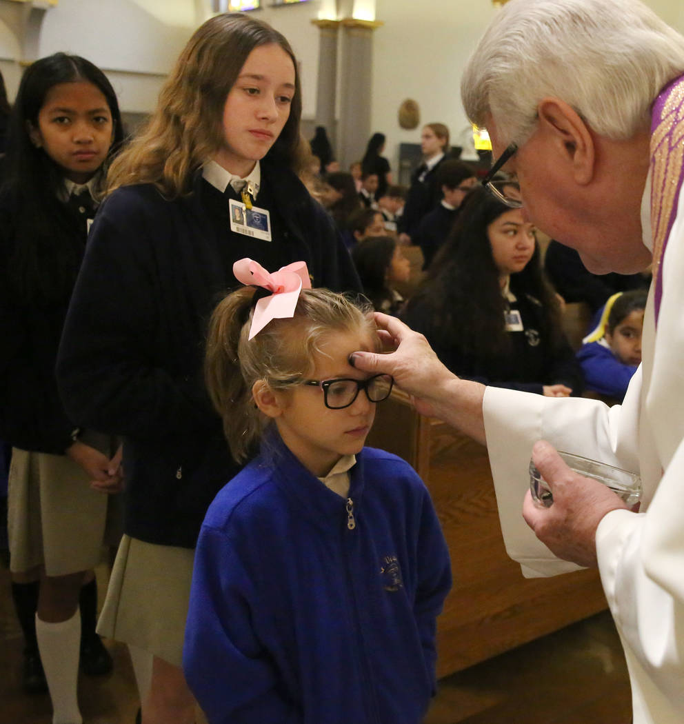 Rev. Larry Lentz applies ashes on a St. Viator Parish School student's forehead at St. Viator Catholic Church during Ash Wednesday on Wednesday, March. 6, 2019, in Las Vegas. Bizuayehu Tesfaye Las ...