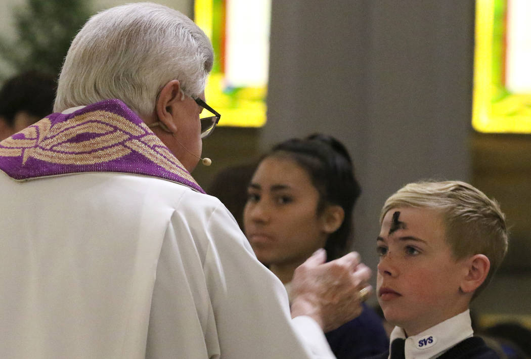 Rev. Larry Lentz applies ashes on St. Viator Parish School student Stryder Ratajczyk's forehead at St. Viator Catholic Church during Ash Wednesday on Wednesday, March. 6, 2019, in Las Vegas. Bizua ...
