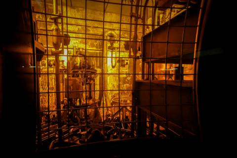 Seen through thick protective glass, shows the area where workers sand-blast the large stainless steel tanks used in the vitrification process to rid them of contaminates at the Defense Waste Proc ...