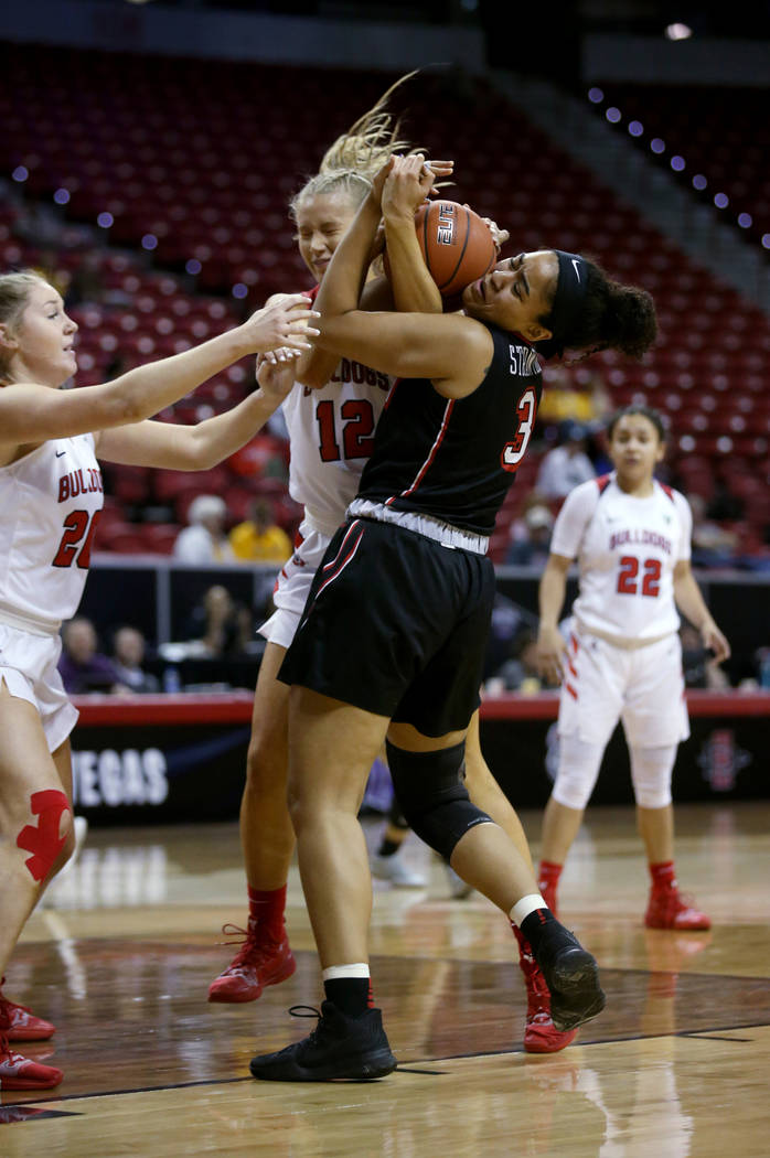 UNLV Lady Rebels forward Paris Strawther (3) battles for the ball with Fresno State Bulldogs forward Genna Ogier (12) in the first period of their quarterfinal game of the Mountain West women's ba ...