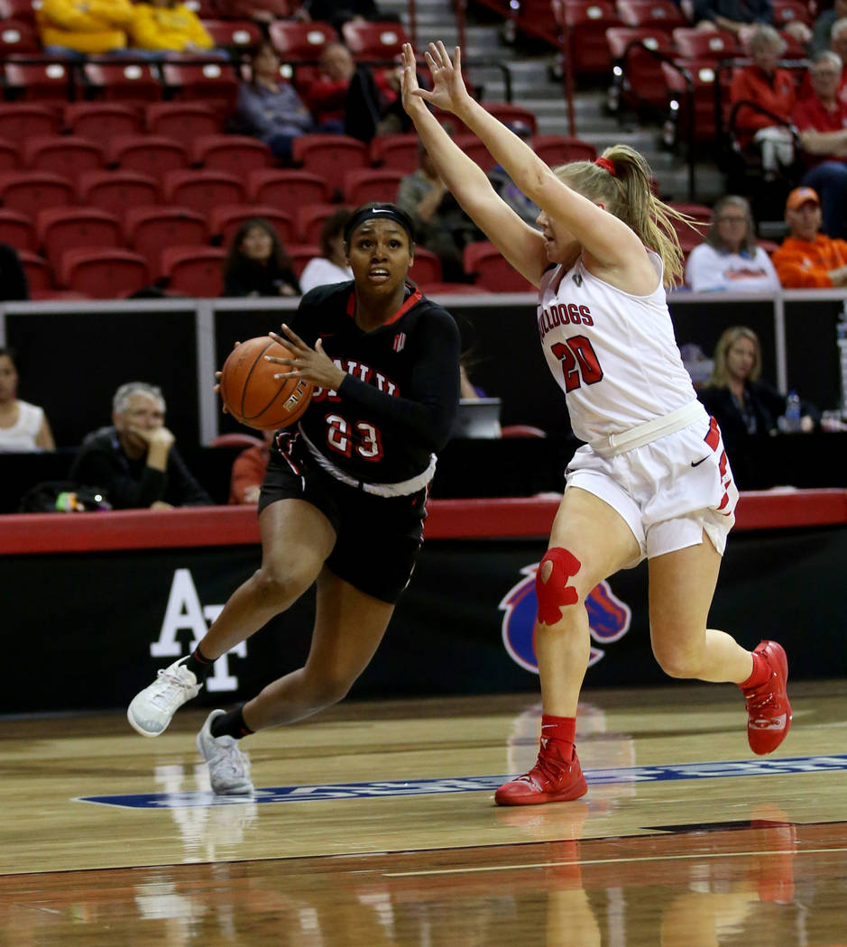 UNLV Lady Rebels forward Jordyn Bell (23) drives past Fresno State Bulldogs guard Bree Delaney (20) in the first quarter of their quarterfinal game of the Mountain West women's basketball tourname ...