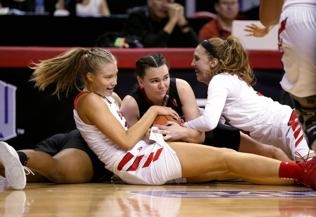 UNLV Lady Rebels forward Alyssa Anderson (20), center, fights for the ball against Fresno State Bulldogs Genna Ogier (12), left, and Kristina Cavey (30) in the second quarter of their quarterfinal ...