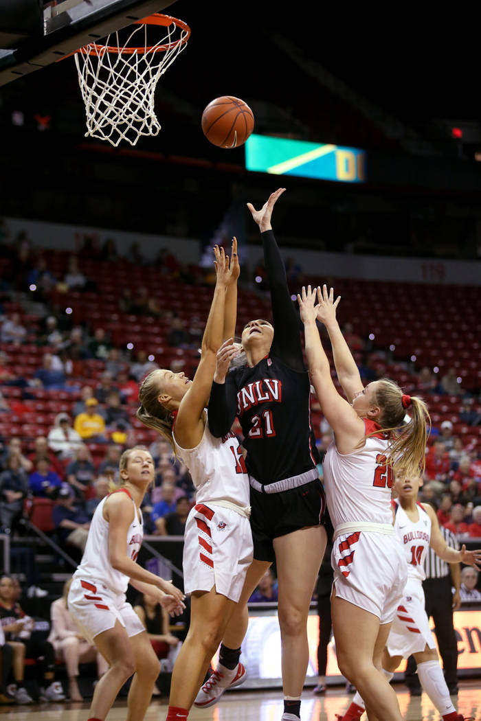 UNLV Lady Rebels forward Katie Powell (21) shoots between Fresno State Bulldogs forward Lydia Friberg (21) and guard Bree Delaney (20) in the third quarter of their quarterfinal game in the Mounta ...