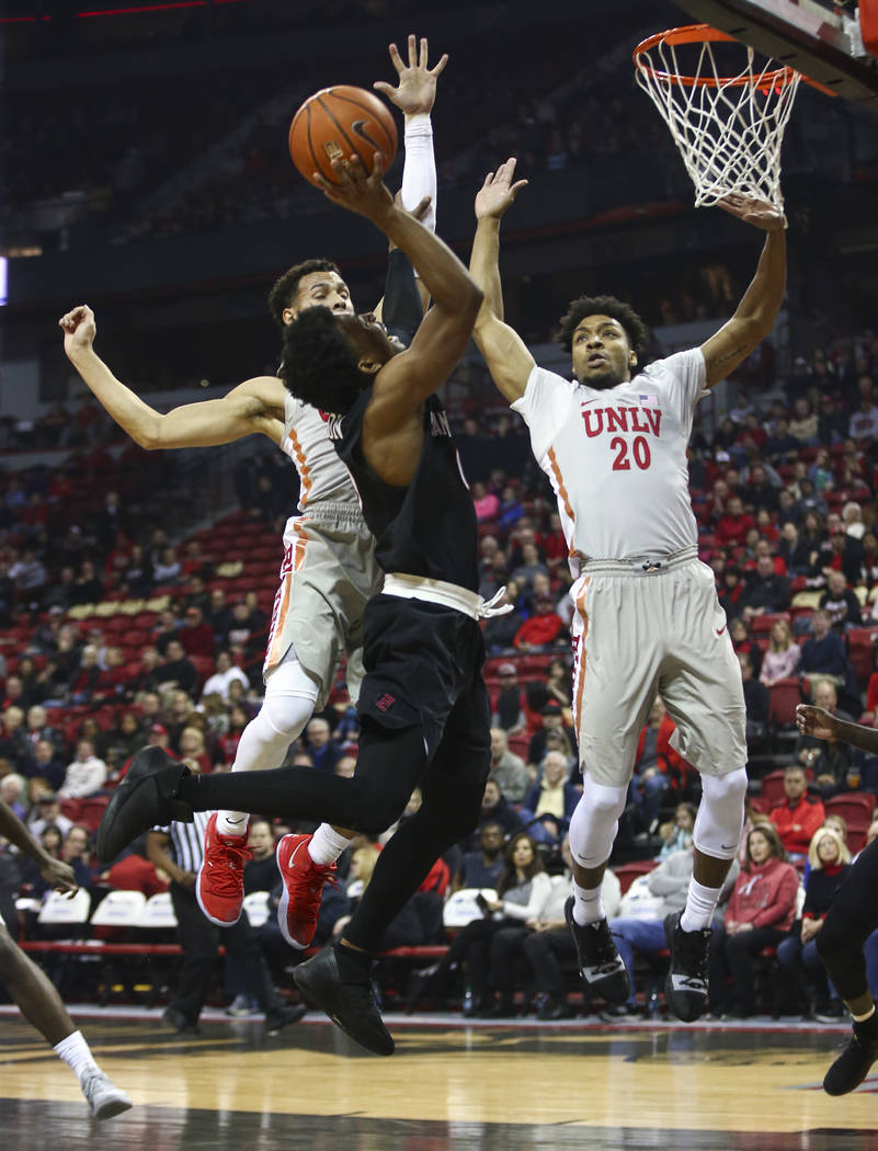 San Diego State Aztecs guard Devin Watson goes to the basket under pressure from UNLV Rebels guard Noah Robotham, left, and forward Nick Blair (20) during the first half of a basketball game at th ...