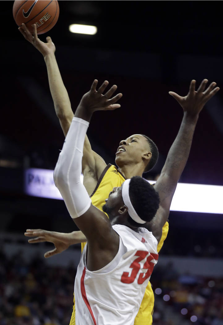 Wyoming's Brandon Porter shoots over New Mexico's Carlton Bragg during the first half of an NCAA college basketball game in the Mountain West Conference tournament Wednesday, March 13, 2019, in La ...