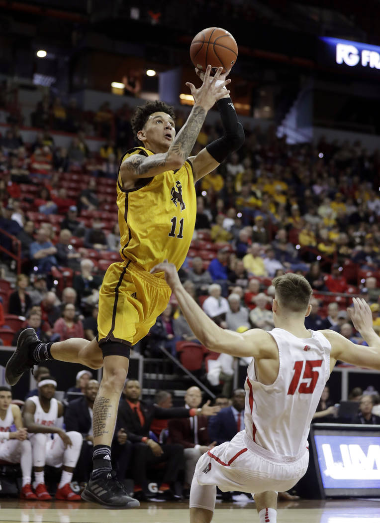 Wyoming's Trace Young shoots over New Mexico's Trey Porter during the first half of an NCAA college basketball game in the Mountain West Conference tournament, Wednesday, March 13, 2019, in Las Ve ...