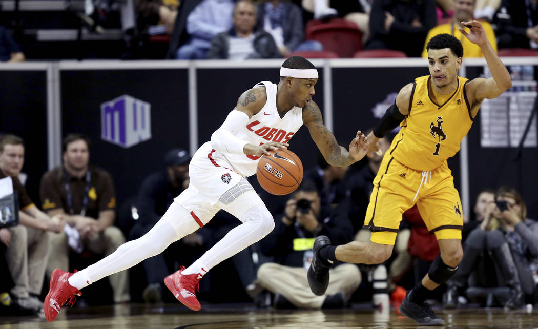 New Mexico's Keith McGee drives while defended by Wyoming's Justin James during the first half of an NCAA college basketball game in the Mountain West Conference tournament, Wednesday, March 13, 2 ...
