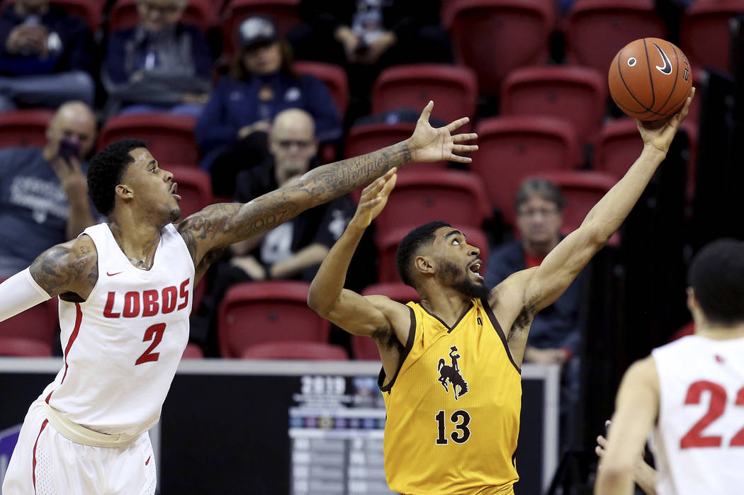 Wyoming's TJ Taylor (13) and New Mexico's Corey Henson (2) reach for a rebound during the first half of an NCAA college basketball game in the Mountain West Conference tournament, Wednesday, March ...