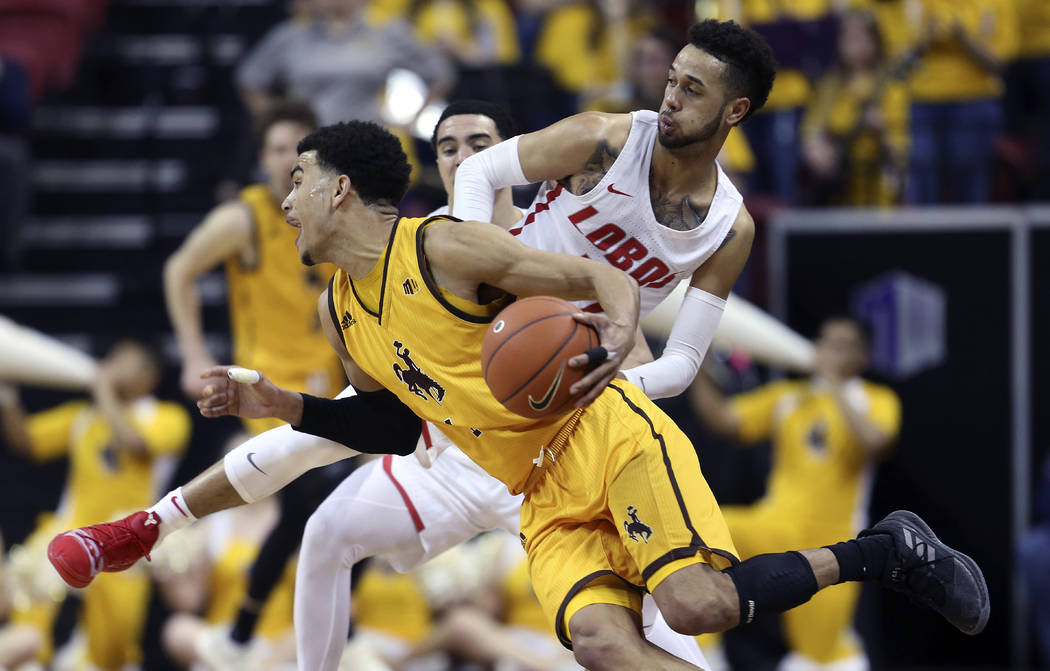 Wyoming's Justin James drives past New Mexico's Anthony Mathis during the second half of an NCAA college basketball game in the Mountain West Conference tournament, Wednesday, March 13, 2019, in L ...