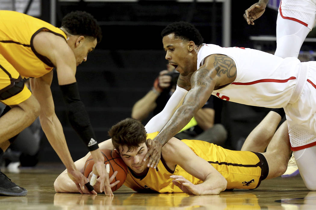 Wyoming's Hunter Thompson, center, Justin James, left, and New Mexico's Corey Henson reach for a loose ball during the first half of an NCAA college basketball game in the Mountain West Conference ...