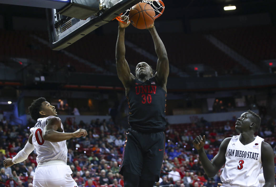 UNLV Rebels forward Jonathan Tchamwa Tchatchoua (30) dunks between San Diego State Aztecs guard Devin Watson (0) and forward Aguek Arop (3) during the first half of a quarterfinal game in the Moun ...